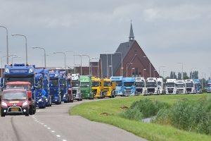 Truckrun met dolblije deelnemers rijd toeterend door Barendrecht