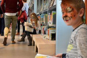 Kinderen lezen een boek in bibliotheek Het Kruispunt tijdens de officiële opening van Het Kruispunt