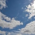 Wolken tegen een blauwe lucht met een zonnetje achter de wolken