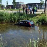 Auto na aanrijding over de kop de sloot in langs Middelweg in Barendrecht